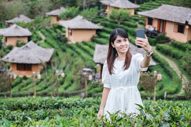 Gelukkig toeristische vrouw in witte jurk foto nemen door mobiele smartphone in prachtige theetuin.