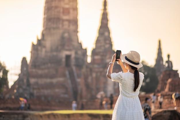 Gelukkig toeristische vrouw in witte jurk foto nemen door mobiele smartphone, tijdens een bezoek aan de wat chaiwatthanaram tempel in ayutthaya historical park, zomer, solo, azië en thailand reizen concept