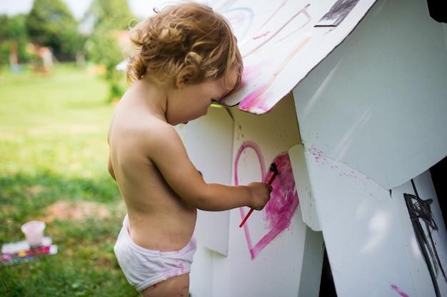 Gelukkig topless klein blond meisje dat in de zomer papieren huis buiten schildert.