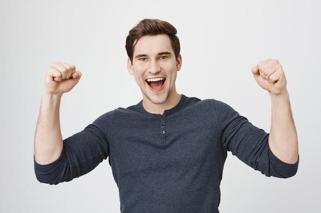 Gelukkig triomfantelijke man bereikt doel, hand opsteken en schreeuwen ja