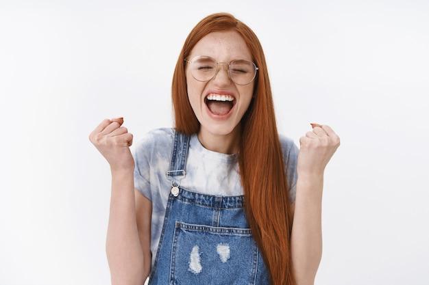 Gelukkig triomfantelijke roodharige tienermeisje kreeg een beurs, maak een vuistpomp, schreeuw ja, vier goed nieuws, winnen, voel de smaakoverwinning, sta op een witte muur