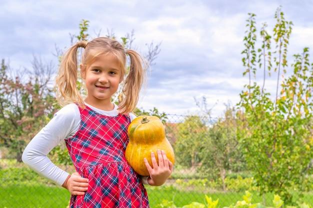 Gelukkig trots klein meisje dat een flanellen jurk draagt en een pompoen vasthoudt op een boerderij