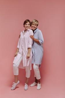Gelukkig twee dames met kort haar in gestreepte lange shirts, witte broeken en coole sneakers glimlachend en knuffelen op geïsoleerde achtergrond.