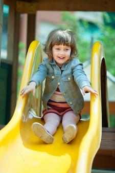 Gelukkig twee jaar meisje in jas op glijbaan