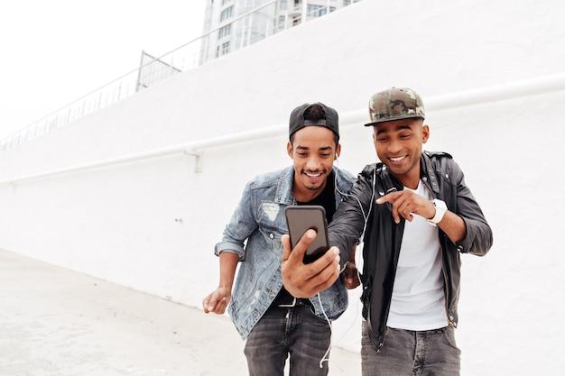 Gelukkig twee jonge afrikaanse mannen vrienden lopen