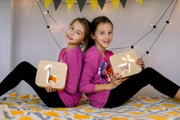 Gelukkig twee lachende schattige 10-jarige meisjes zusters rug aan rug zitten en houden van houten nachtlampjes met uitgesneden afbeeldingen.