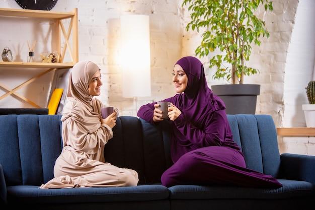 Gelukkig twee moslimvrouwen thuis tijdens de les, studeren in de buurt van computer, online onderwijs