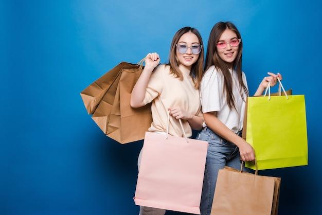 Gelukkig twee vrouwen met kleurrijke boodschappentassen op blauwe muur