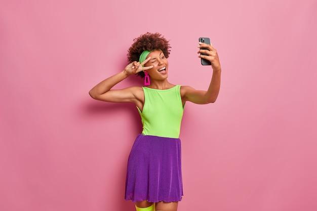 Gelukkig uitgaande vrouw maakt overwinning gebaar, oog knipoogt en vormt op de camera van de smartphone, neemt selfie, gekleed in kleurrijke outfit
