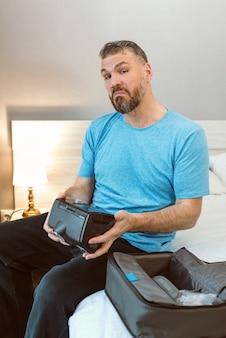 Gelukkig uitgeslapen man met chronische ademhalingsproblemen na gebruik van cpap-machine zittend op het bed