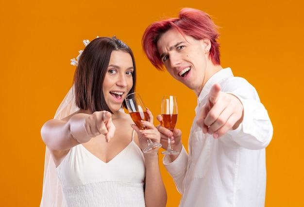 Gelukkig uitziende bruidspaar bruidegom en bruid in trouwjurk glimlachend vrolijk poseren samen met glazen champagne wijzend met wijsvingers naar voren