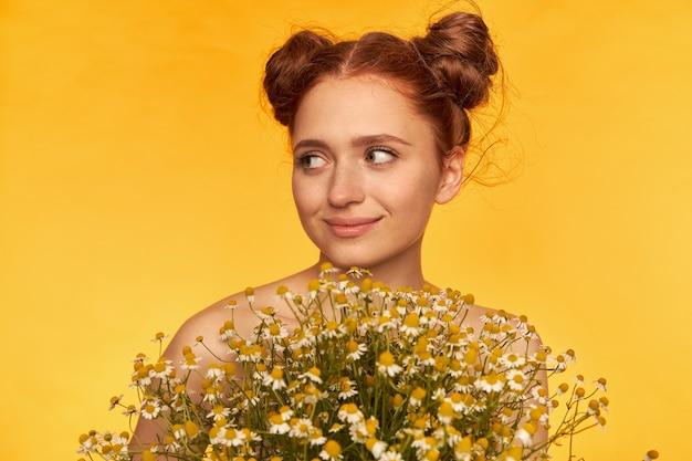 Gelukkig uitziende rood haar vrouw met twee broodjes. kapsel. houd een boeket bloemen vast, glimlach en kijk naar links