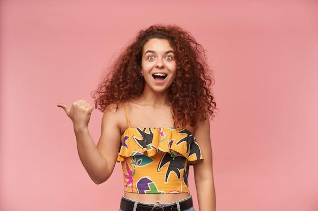 Gelukkig uitziende vrouw met krullend gemberhaar, gekleed in kleurrijke off-shoulder blouse