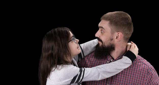 Gelukkig vader en dochter knuffelen op zwarte achtergrond.