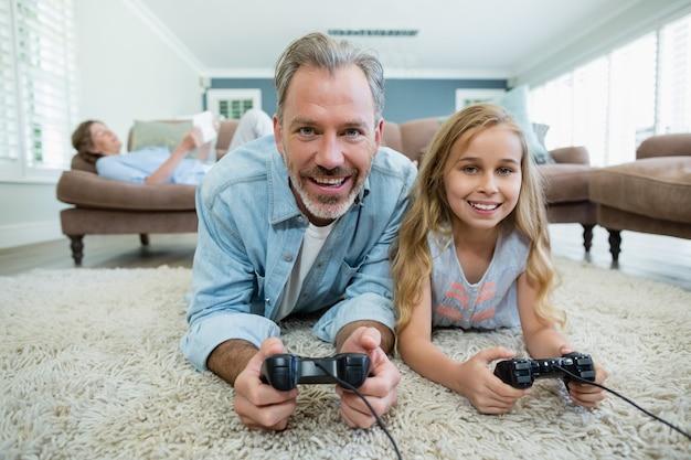 Gelukkig vader en dochter spelen van videogame terwijl liggend op de vloer in de woonkamer