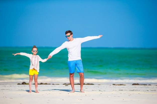 Gelukkig vader en kind samen op wit tropisch strand