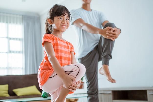 Gelukkig vader en kind sporten samen. portret van gezonde familie en dochter training thuis uitrekken