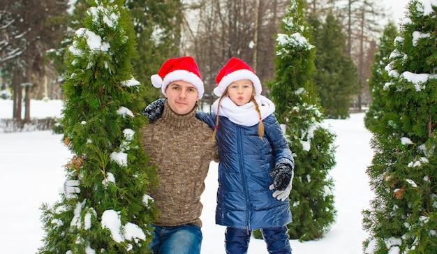 Gelukkig vader en meisje in kerstmanhoeden met kerstmisboom openlucht