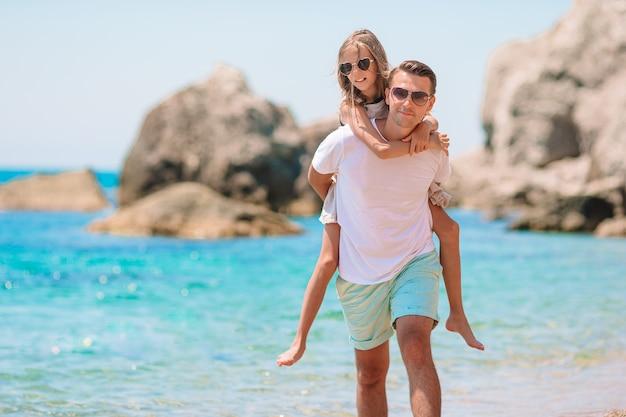 Gelukkig vader en meisje op het witte zandstrand hebben samen plezier