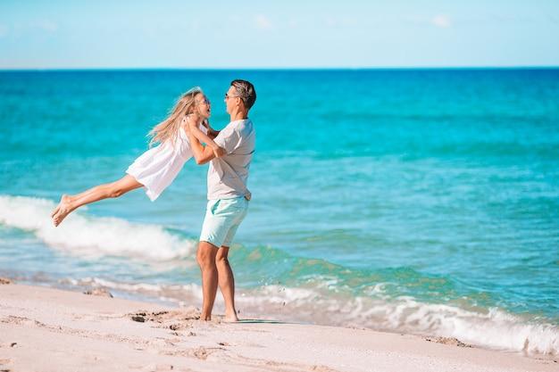 Gelukkig vader en meisje op wit zandstrand samen plezier hebben