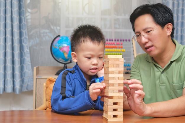 Gelukkig vader en schattige kleine aziatische jongenskind opgewonden met houten blok spel, vader en zoon tijd samen doorbrengen
