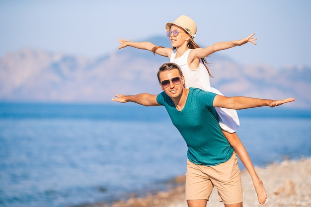 Gelukkig vader en zijn schattige dochtertje op wit zandstrand met plezier