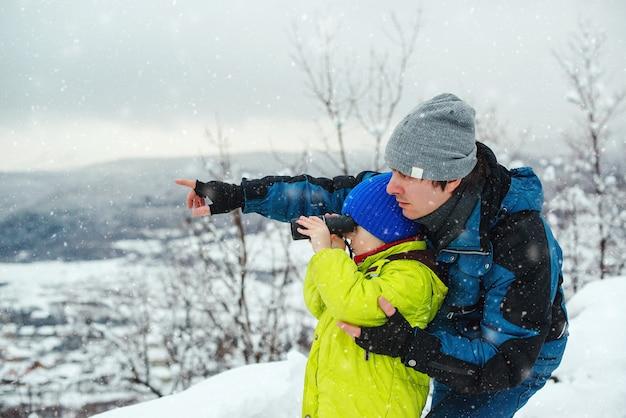 Gelukkig vader en zoon in winter woud. kid op zoek naar monoculair. familie wintervakantie