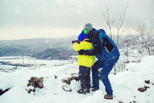 Gelukkig vader en zoon in winter woud. kid op zoek naar monoculair. familie wintervakantie.