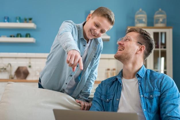 Gelukkig vader en zoon met behulp van de laptop