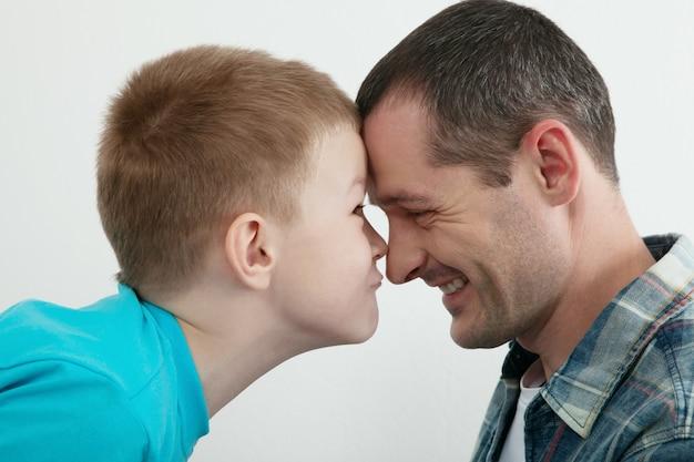 Gelukkig vader en zoon spelen en lachen samen thuis.