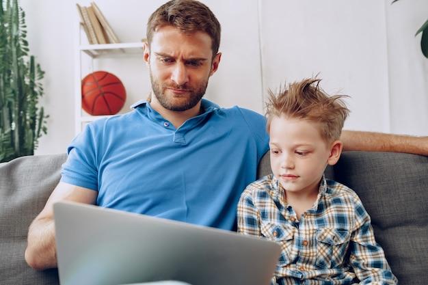 Gelukkig vader en zoon zittend op de bank en kijken naar iets op laptop