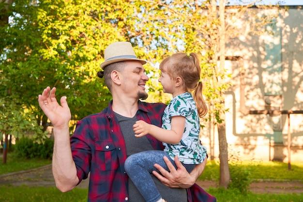 Gelukkig vader heeft plezier met zijn dochtertje man draagt baby vrouw in zijn armen