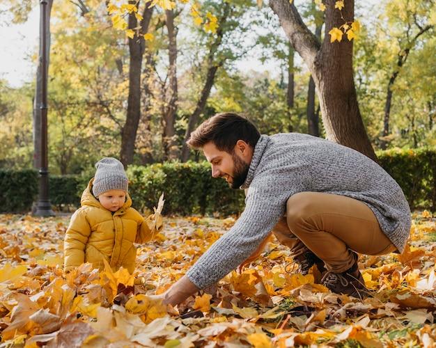 Gelukkig vader met baby buiten in de natuur