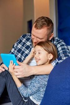 Gelukkig vader met dochter met behulp van tabletcomputer in de woonkamer, op de bank thuis