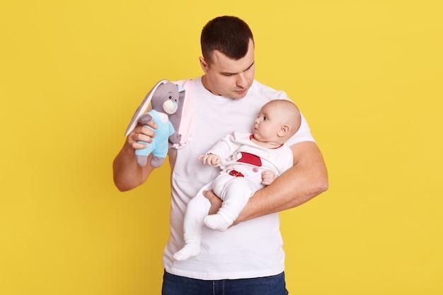 Gelukkig vader spelen met zijn baby met heldere rammelaar