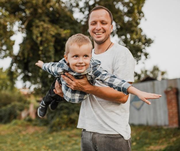 Gelukkig vader zijn zoon in de armen houden en spelen