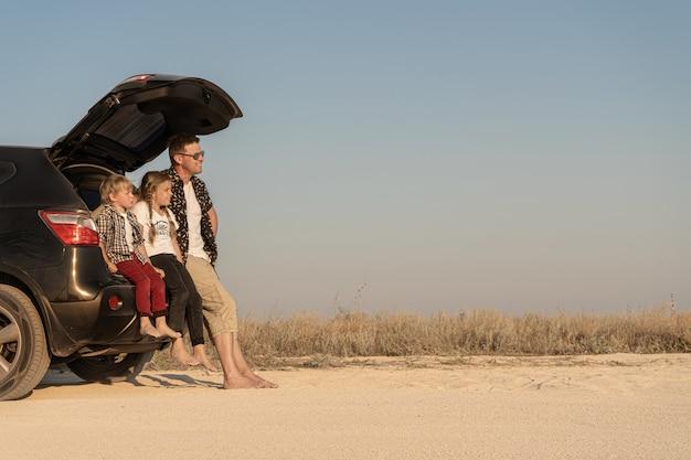 Gelukkig vader zit in de kofferbak van de auto in de buurt van zoon en dochter in casual kleding