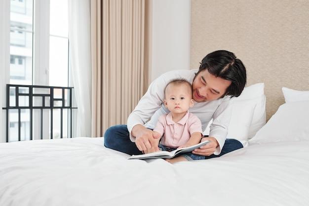 Gelukkig vader zittend op bed en leesboek voor zijn schattige zoontje