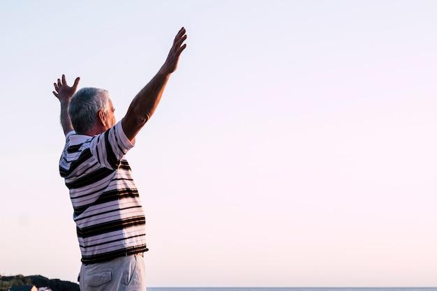 Gelukkig van de mens die alleen staat met opgeheven armen tijdens de prachtige zonsopgang bij de zonsondergang. genieten met de natuur - gepensioneerde man voelt zich goed en heeft plezier - senior kaukasisch 60s vrijheidsconcept