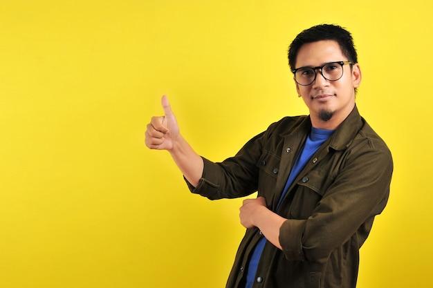 Gelukkig van jonge aziatische man die duimen opgeeft, ruimte kopieert, geïsoleerd op gele achtergrond