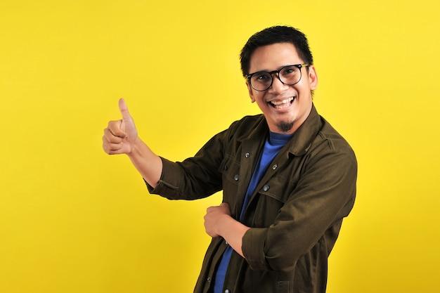 Gelukkig van jonge aziatische man die lacht en duimen opgeeft, kopieer ruimte, geïsoleerd op gele achtergrond