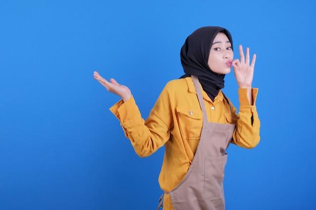 Gelukkig van mooie vrouw die schort draagt die heerlijk gebaar toont