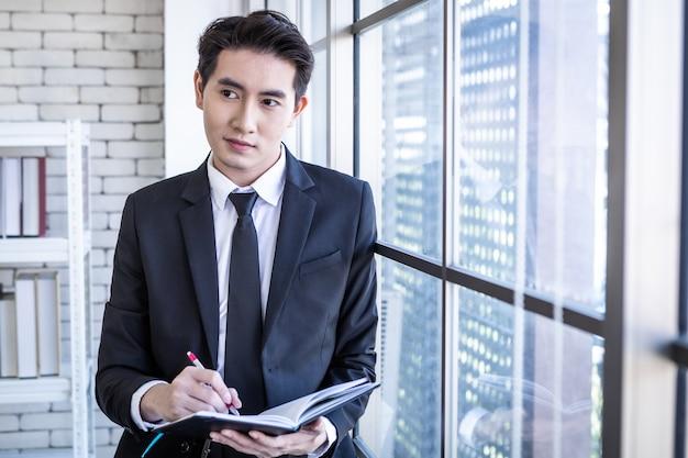 Gelukkig van succesvolle aziatische jonge zakenman die werkt met lees de notitie die is opgenomen in het businessplan-notebook in de kantoorruimte kopieerruimte achtergrond.