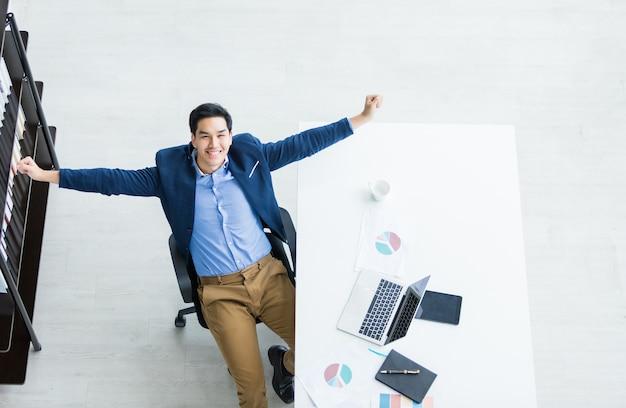 Gelukkig van succesvolle aziatische jonge zakenman op laptopcomputer