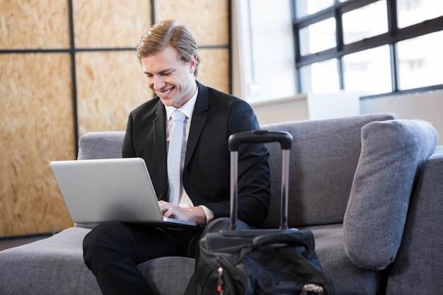 Gelukkig van zakenmanzitting op bank en het gebruiken van laptop in bureau