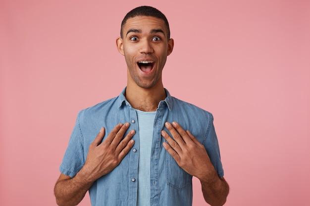 Gelukkig verbaasd jonge aantrekkelijke donkere man in een leeg shirt, kijkt naar de camera met wijd open mond en ogen, staat op roze achtergrond met palmen op onbeleefd.