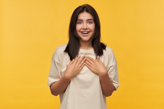 Gelukkig verbaasde brunette jonge vrouw in witte t-shirt houdt handen op de borst en kijkt verbaasd over gele muur dankbaar gebaar