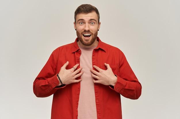 Gelukkig verbaasde jonge bebaarde man in rood shirt kijkt verbaasd en wijst naar zichzelf met beide handen over een witte muur