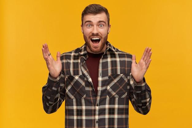 Gelukkig verbaasde jongeman in geruit overhemd met baard en opemed mond houdt de handen omhoog en kijkt verbaasd over de gele muur