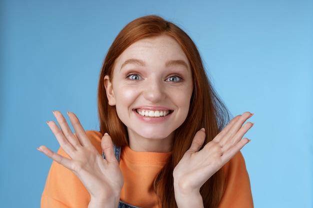 Gelukkig verheugend emotioneel jong glimlachend roodharig meisje blauwe ogen krijgen opwindend nieuws grijnzend juichen gelukkig handen opsteken opgewonden grote ogen verrast geaccepteerd beroemde universiteit blauwe achtergrond